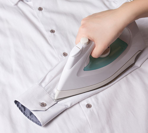An image of an employee from Queens Drive Laundry ironing a shirt.