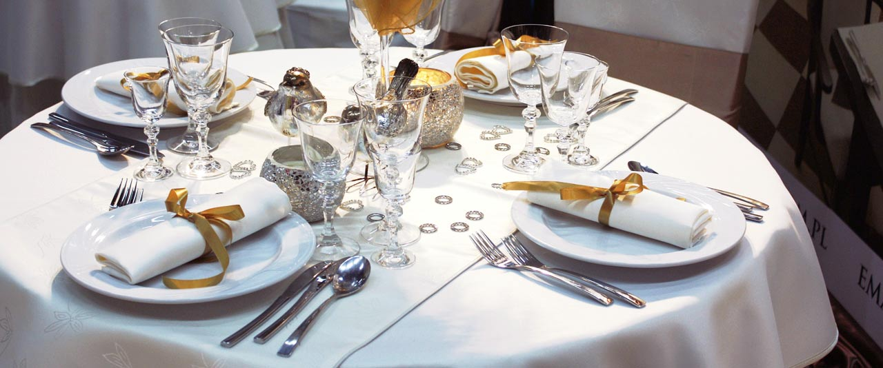 An image of a table set for dinner with white linen hired from Queens Drive Laundry
