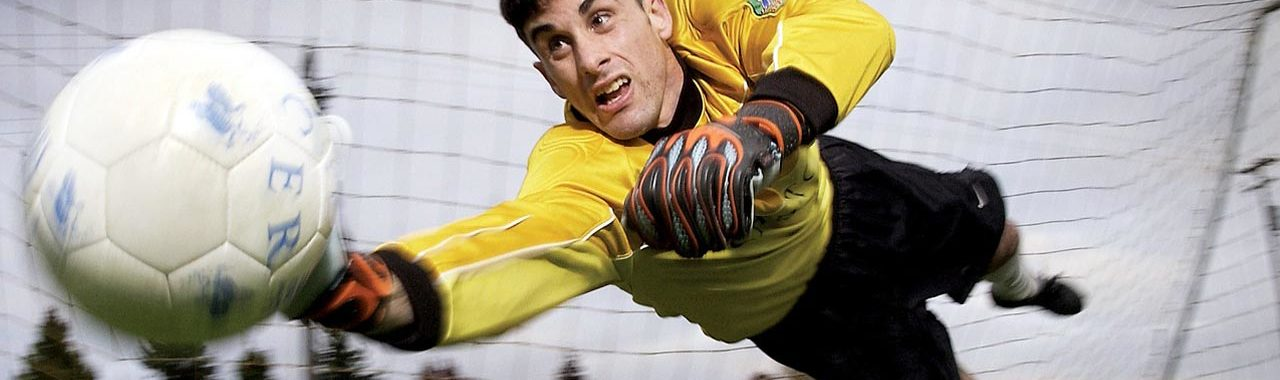 An image showing a goal keeper diving for a football wearing a clean sports kit Laudered by Queens Drive Laundry