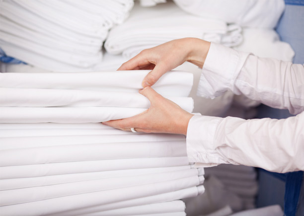 An image of a folded pile of white linen being used for hotel bedding