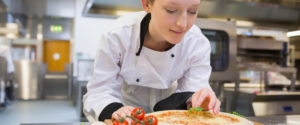 An image of a Chef making a pizza, wearing clean protective clothing