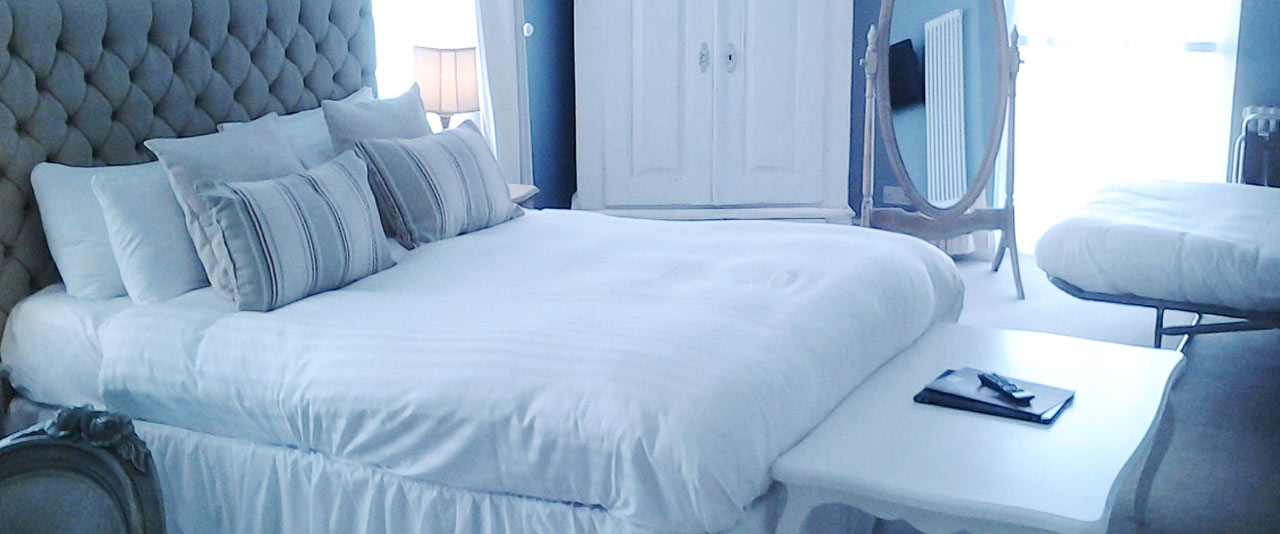 An image of a stylish tidy bedroom with white Hotel Linen Hire from Queens Drive Laundry