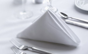 An image of white linen napkin being used on a dining table with silver cutlery and wine glasses in the background
