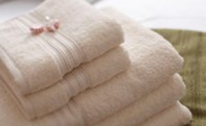 An image showing three cream folded body towels and two cream folded hand towels hired from Queens Drive Laundry
