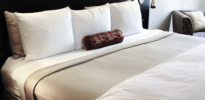 An image of a made bed using linen hired from Queens Drive Laundry