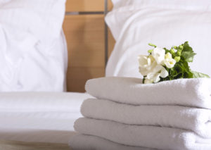 An image showing white hotel laundry folded on a bed with a stem of white flowers placed on top