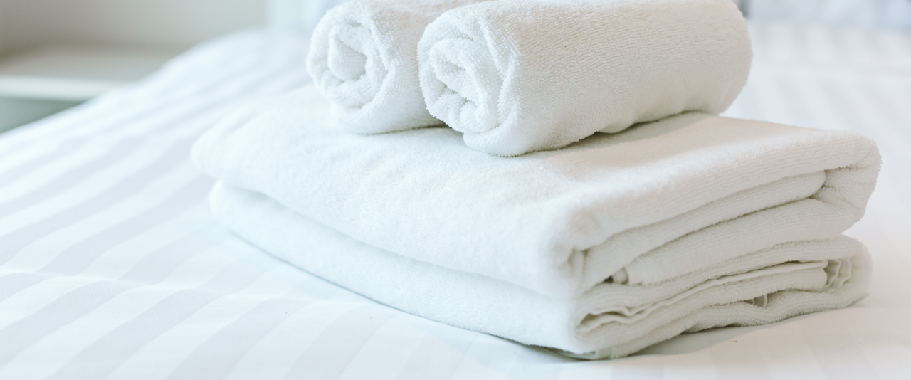 An image showing high quality and durable white towels folded on a hotel bed serviced by Queens Drive Laundry