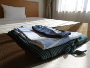 An image showing a bed with white sheets and fresh laundry folded on top.