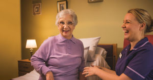 An image of a care home nurse sitting beside an eldery resident that is sat on a bed with freshly laundered bed sheets.