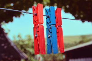 An image of laundry pegs hanging on a washing line.