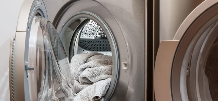 An image of towels coming out of an open door on a washing machine.