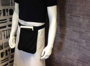 An image of a mannequin wearing a long line white waist apron and a black money pouch.