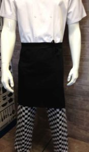 An image of a mannequin wearing a double breasted chef jacket tucked into a black waist apron and chequered chef trousers.