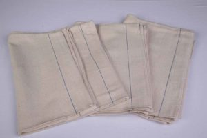 An image of four cream heavy duty oven cloths with a single blue stripe marking one edge.