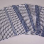 An image of four blue and white chequered Wonder dry tea towels, available to purchase or hire from Queens Drive Laundry.