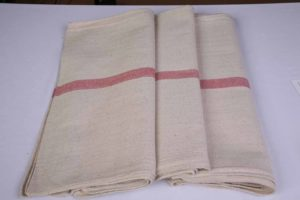 An image of three cream waiters cloths with a red stripe, folded up neatly.