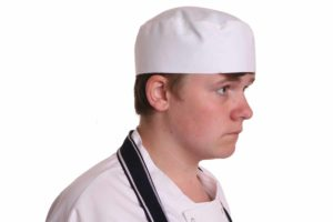 An image of a male chef wearing a white chef skull cap.