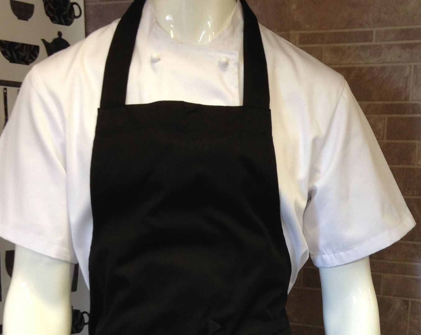 An image of a mannequin wearing a white double breasted chef jacket with French knot buttons, underneath a black apron.