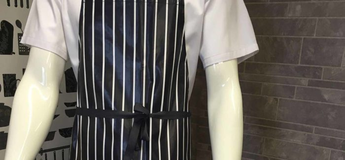 An image a mannequin displaying a white double breasted chef jacket, under a navy and white striped apron.