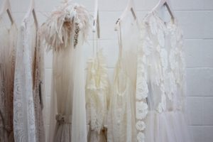 An image of several wedding dresses hanging up that need to be dry cleaned.