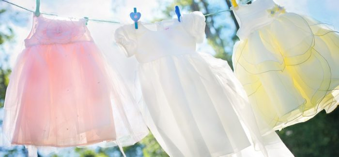 An image of three girls dresses hanging on washing line and blowing in the wind, one is pink, one is white and one is pale yellow.